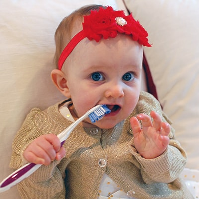 Little baby playing with a toothbrush to showcase going to the dentist is fun for kiddos