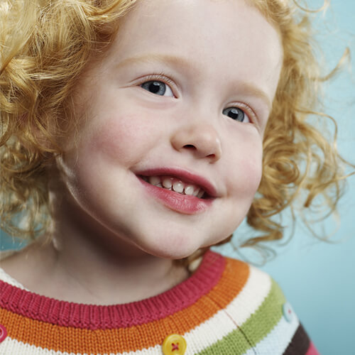 A young child with freckles and curly red hair and a beautiful smile as she has been seeing her pediatric dentistry regularly.