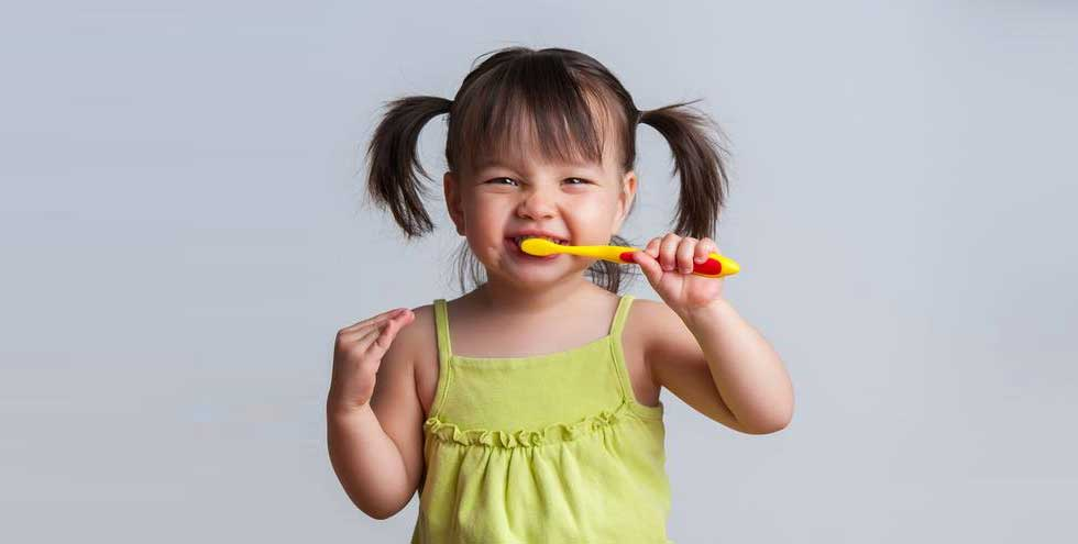 Little girl brushing her teeth, practicing excellent oral hygiene